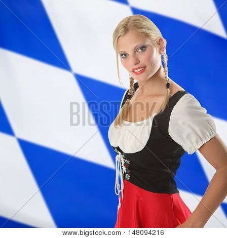 Smiling bavarian woman in traditional dirndl clothing with a bavarian flag in the background