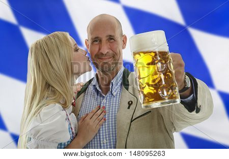 Bavarian Oktoberfest Couple man holding a beer mug and gets kissed on his cheek