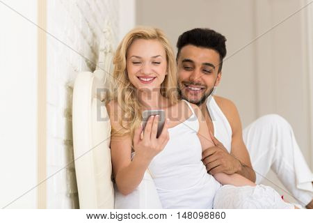 Young Couple Lying In Bed, Happy Smile Hispanic Man And Woman Using Cell Smart Phone, Lovers In Bedroom