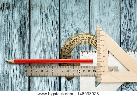Drafting tools on wooden background in closeup