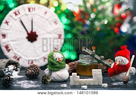 Handmade toy snowman and snowgirl of yarn skeins making stove of sugar and honey over background of knitted clock and shiny Christmas decorations. Color toning