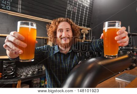 Happy Smiling Barman Hold Two Beer Glasses, Stand At Counter, Bartender Serving Order, Pub Worker Workplace