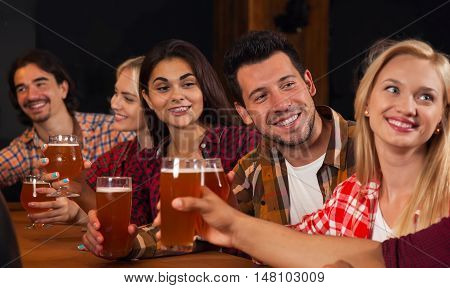 Young People Group In Bar, Hold Beer Glasses Speaking, Friends Sitting At Wooden Table Chatting Pub, Friends Happy Smiling Communication Party Celebration