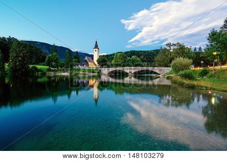 BOHINJ LAKE SLOVENIA - AUGUST 22 2016: Church of St. John the Baptist at Bohinj Lake is over 700 years old and is a beautiful example of Middle Age architecture and fresco painting in Slovenia.