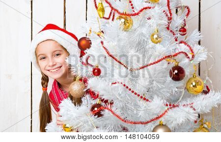 smiling little girl in red hat peeking out from behind a decorated new year tree