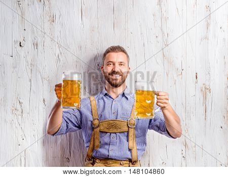 Handsome young man in traditional bavarian clothes holding two mugs of beer. Oktoberfest. Studio shot on white wooden background.