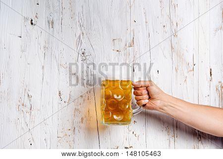 Hand of unrecognizable man holding a beer mug. Oktoberfest. Studio shot on white wooden background. Copy space.
