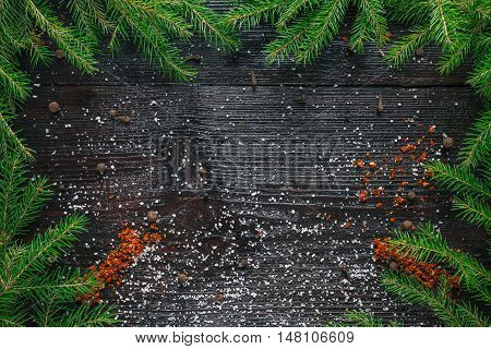 Frame of evergreen branches and spices on the dark wood surface