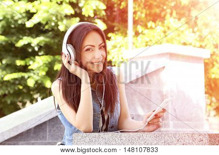 Young Beautiful Woman Listening Music With Headphones In The Park