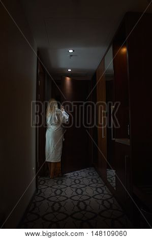 Blonde Woman with Bathrobe opens a Door in Hotel Room
