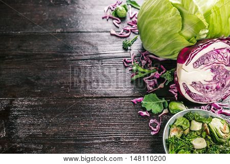 Green and red cabbage, broccoli and brussel sprouts, fresh and cooked on the dark wooden surface