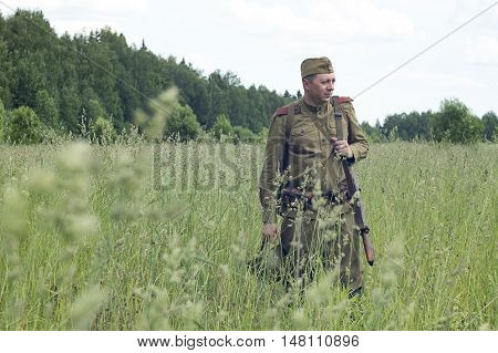 Russian soldiers standing in a field with a rifle. Reconstruction 1941-1945