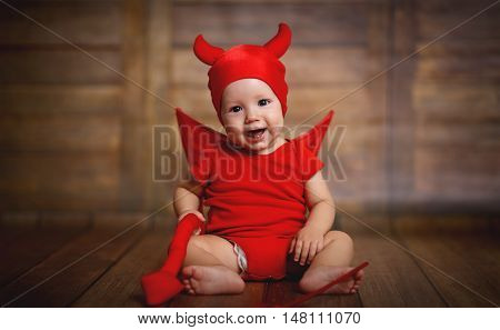 funny baby in devil halloween costume with horns on a dark wooden background