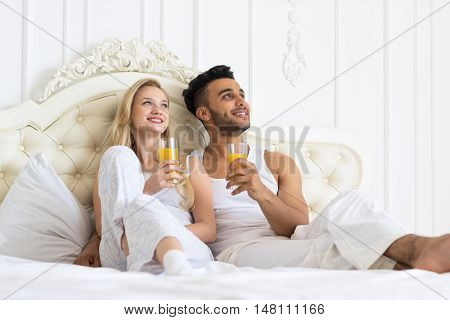 Young Couple Drink Orange Juice Sitting In Bed, Happy Smile Young Hispanic Man And Woman Look Up Lovers Hold Glasses Bedroom