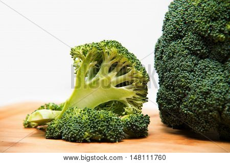 Close Up On Fresh Broccoli Solated On Wooden And White Background