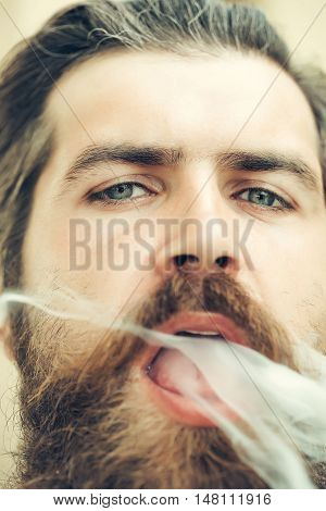 Young man hipster smoker with beard on face open exhale tobacco smoke from open mouth closeup