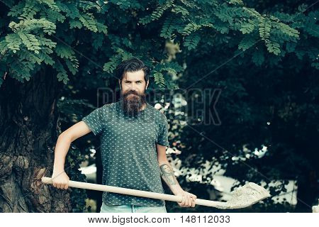 Young man bearded brutal hipster with smiling face in casual clothes standing with shovel of sand on green oak tree natural background