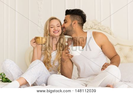 Young Couple Drink Coffee Sitting In Bed, Happy Smile Young Hispanic Man Kisses Woman Lovers Hold Cups Bedroom