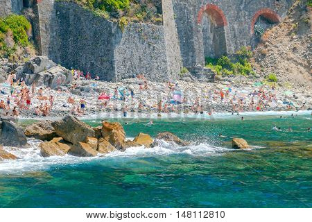 Riomaggiore. Italy - July 24, 2016: Vacationers on a pebble beach in the medieval village of Riomaggiore. The old towns in the Cinque Terre National Park are highly popular among tourists.