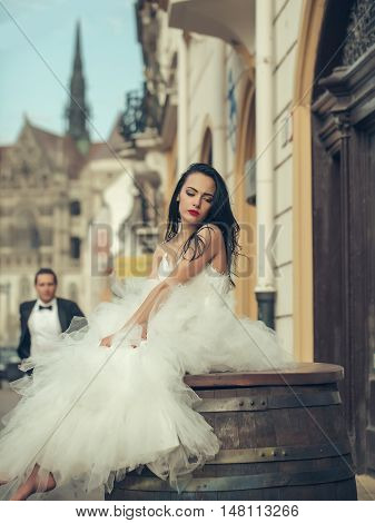 Beautiful bride brunette woman with long hair in fashion white wedding dress sits on wooden barrel and waits for groom on streetscape