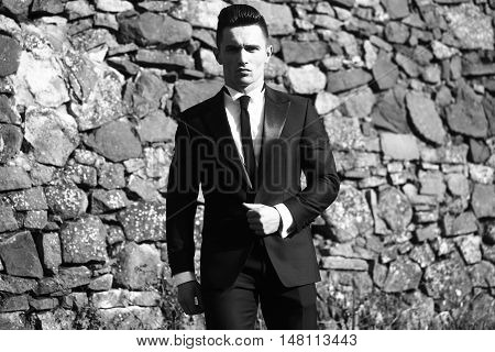 Man young handsome elegant model wears suit shirt with skinny necktie looks in camera poses outdoor black and white on masonry background