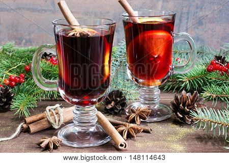 christmas mulled wine with cinnamon sticks anise and orange on wooden table background with fir branches and pine cones