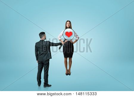 Businessman looking through woman's chest with a magnifier and seeing a heart inside. Business staff. Relationsip at work. Employment issues.