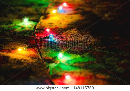 Multi-colored Christmas garland in the dark at a low exposition