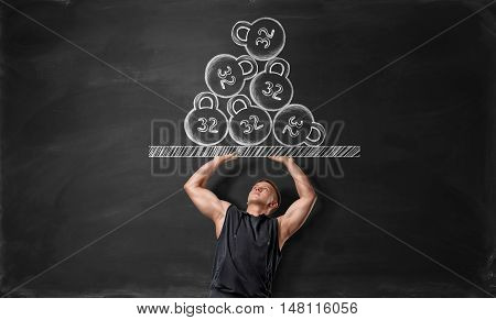 Muscled young man pushing off hand drawn surface with kettlebells. Weightlifting. Heavy weight. Picture on blackboard. Strength and beauty.