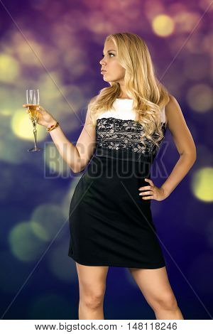 a young woman with loose long blond hair in a black and white dress is holding a glass of wine in her hand in the background of sunbeams