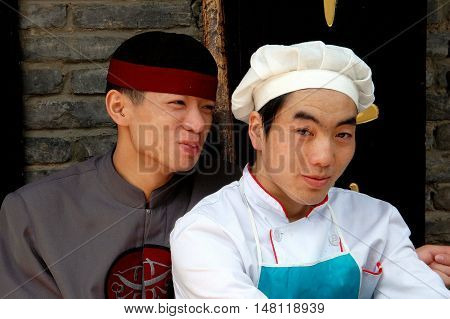 Kunming China - April 24 2006: Waiter and chef employees at a Chinese restaurant taking a break on Yonng People's Road