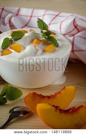 A bowl of yoghurt with pieces of nectarines and peppermint