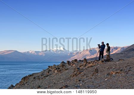 LADAKH, INDIA - JUNY 20, 2012: Tourists with camera watching on Tso Moriri Lake in Ladakh, Jammu and Kashmir, North India