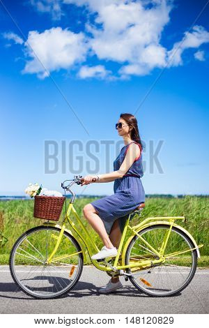 Side View Of Beautiful Woman Riding Retro Bicycle In Countryside