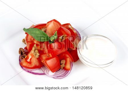tomato salad with basil red onion and sour cream on a white background
