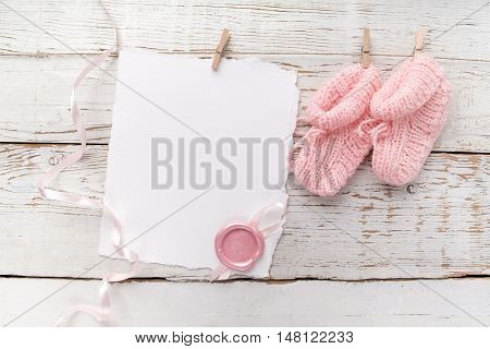 pink baby's booties. Small girls sock, blank card on white wooden background