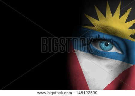 A young female with the flag of Antigua and Barbuda painted on her face on her way to a sporting event to show her support.