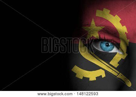A young female with the flag of Angola painted on her face on her way to a sporting event to show her support.