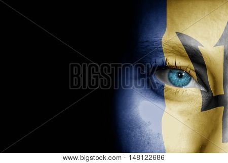A young female with the flag of Barbados painted on her face on her way to a sporting event to show her support.
