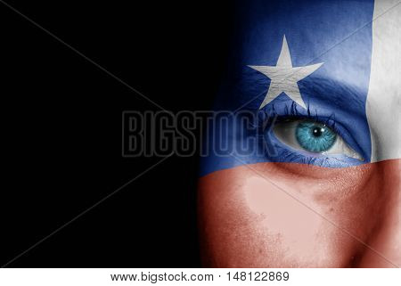 A young female with the flag of Chile painted on her face on her way to a sporting event to show her support.