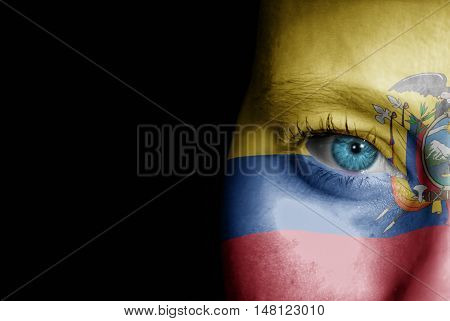 A young female with the flag of Ecuador painted on her face on her way to a sporting event to show her support.