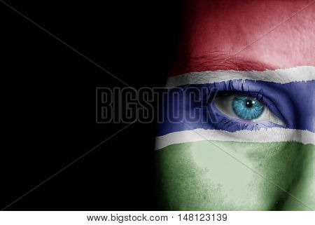 A young female with the flag of Gambia painted on her face on her way to a sporting event to show her support.