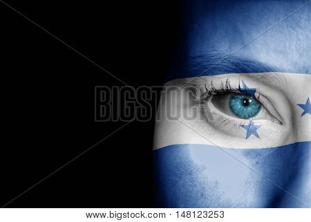 A young female with the flag of Honduras painted on her face on her way to a sporting event to show her support.