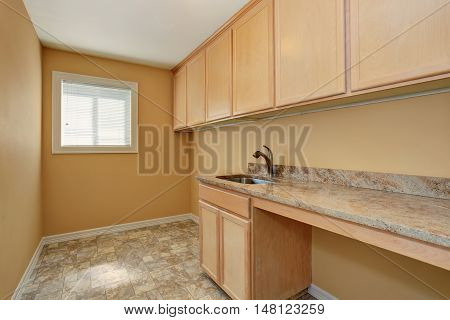 Empty Laundry Room With Cabinets With Granite Counter Top And Sink
