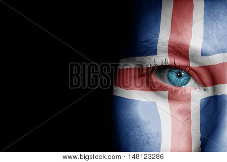 A young female with the flag of Iceland painted on her face on her way to a sporting event to show her support.