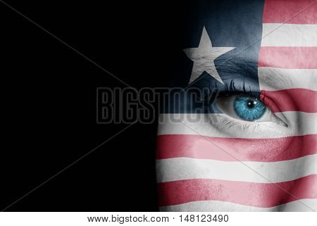 A young female with the flag of Liberia painted on her face on her way to a sporting event to show her support.