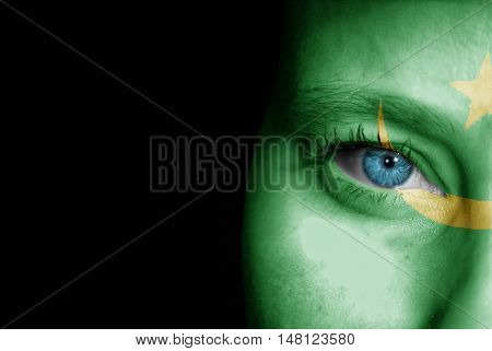A young female with the flag of Mauritania painted on her face on her way to a sporting event to show her support.
