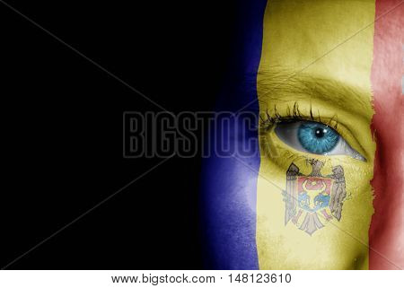 A young female with the flag of Moldova painted on her face on her way to a sporting event to show her support.