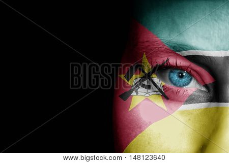 A young female with the flag of Mozambique painted on her face on her way to a sporting event to show her support.