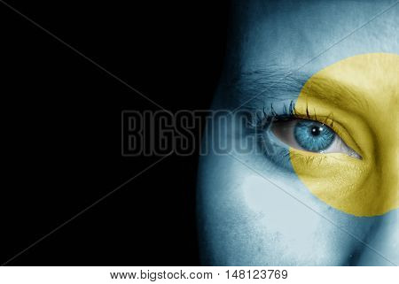 A young female with the flag of Palau painted on her face on her way to a sporting event to show her support.